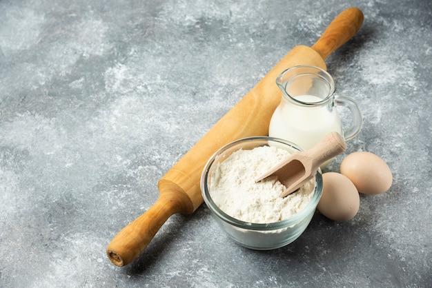 Mąka, jajka, mleko i wałek do ciasta na marmurze.