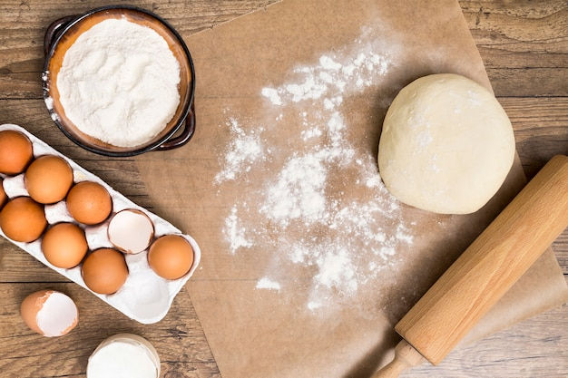 Mąka; karton jajek; ciasto; wałek do ciasta na pergaminie ponad drewnianym biurkiem