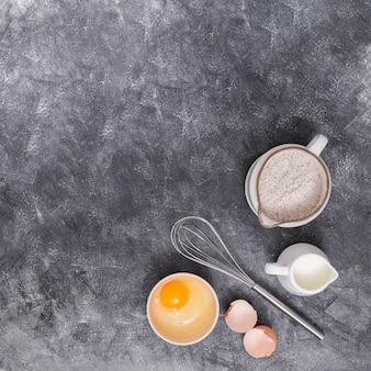 Mąka; mleko; jaja i trzepaczki na rogu teksturowanego tła