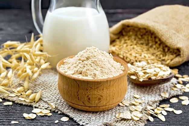 Mąka owsiana w misce, mleko w dzbanku, płatki owsiane łyżką na płótnie, ziarno w torbie, łodygi owsiane na tle deski