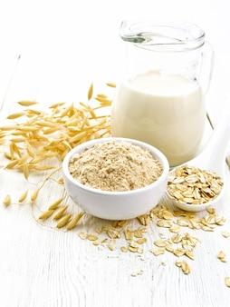 Mąka owsiana w misce, mleko w dzbanku, płatki owsiane na łyżce, łodyżki owsiane na tle jasnego drewnianego stołu
