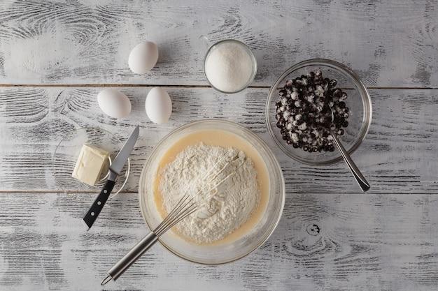 Mąka pełnoziarnista w białej misce, mleko, jajka na lekkim drewnianym stole