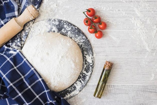 Mąka posypana chlebem z ciasta; pomidory koktajlowe; rozmaryn i wałki do ciasta na drewnianej desce
