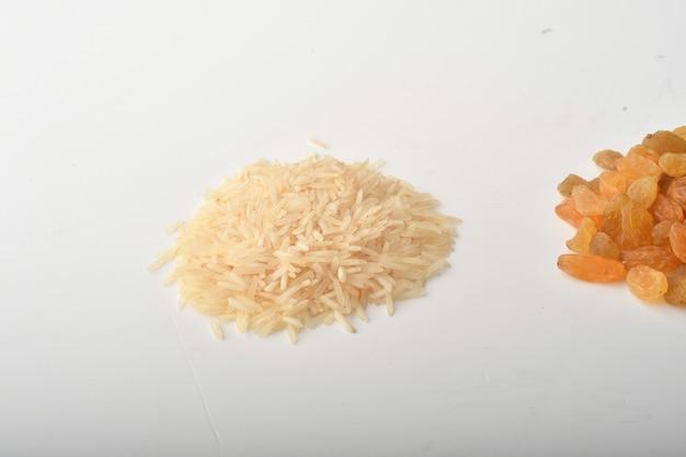 Mąka, pszenica, ryż, rodzynki i monety na białym tle