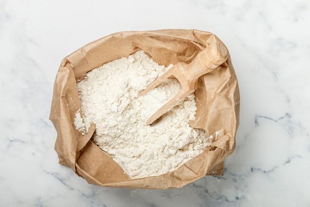 Mąka pszenna i drewniana miarka w papierowej torbie na marmurowym stole, piekarni pojęcie