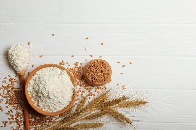 Mąka pszenna i kłosy pszenicy na jasnym tle