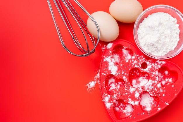 Mąka pszenna, naczynie do pieczenia i trzepaczki do ciastek na śniadanie. walentynki.
