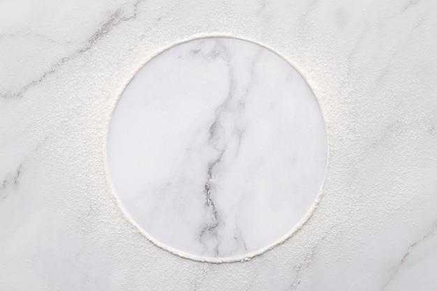 Mąka pszenna rozproszona na białym tle marmuru. posypane koło mąki pszennej na białym tle.