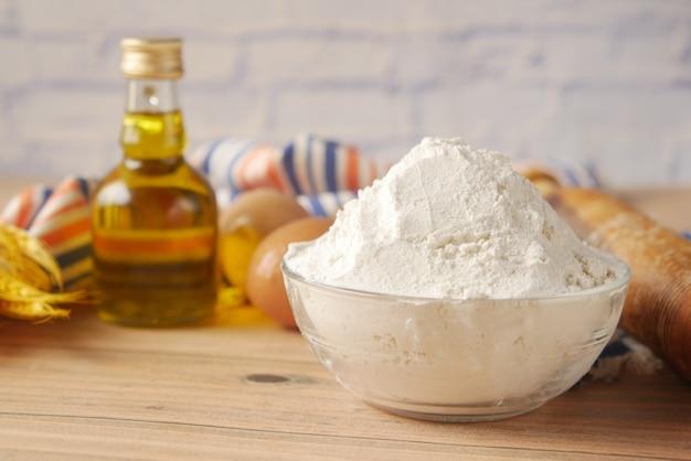 Mąka pszenna w misce , jajko i olej na stole
