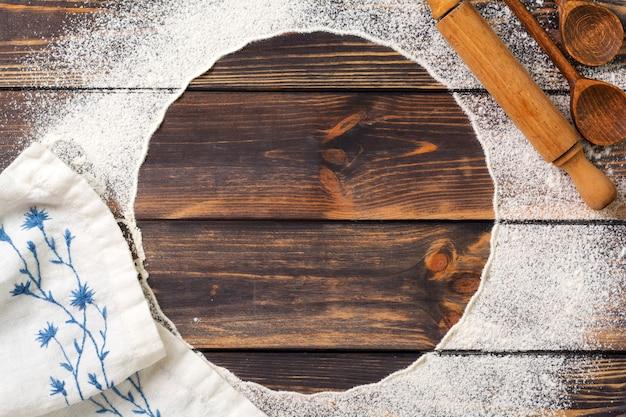 Mąka rozsypana w formie koła, wałka do ciasta i biała lniana serwetka na starym drewnianym tle. miejsce na tekst. tło do pieczenia