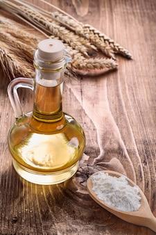 Mąka w drewnianej łyżce butelka oleju i uszy