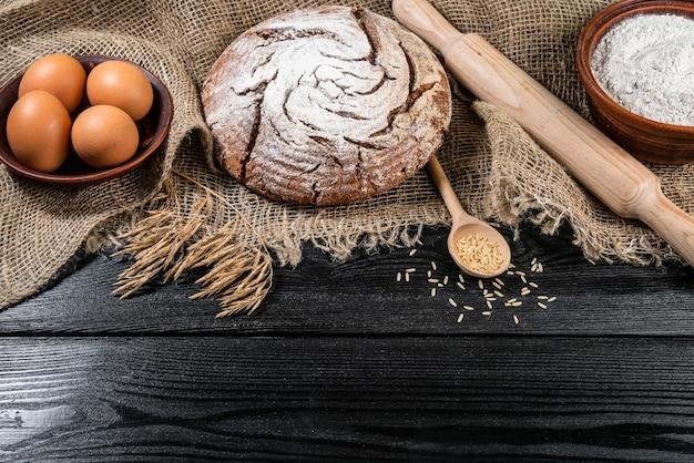 Mąka w drewnianej misce na ciemnym drewnianym stole z spikelets pszenicy, jaj i mleka, widok z góry z miejsca na kopię