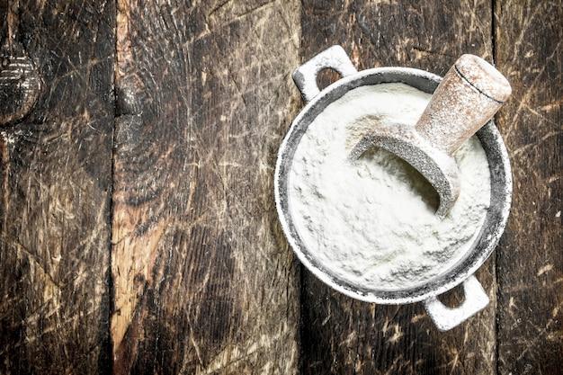 Mąka w misce. na drewnianym tle.
