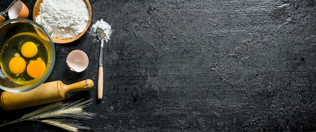 Mąka z jajkami w miseczkach. na czarnej powierzchni rustykalnej