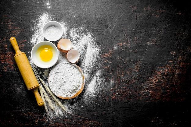Mąka z jajkiem i wałkiem do ciasta. na ciemnej rustykalnej powierzchni