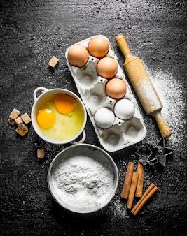 Mąka z jajkiem, kawałkami cukru cynamonowego na czarnym rustykalnym stole