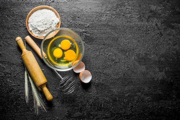 Mąka z jajkiem, trzepaczką i wałkiem do ciasta na czarnym rustykalnym stole