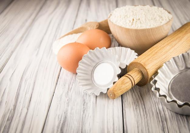 Mąka z naczyniami do pieczenia na drewnianym stole