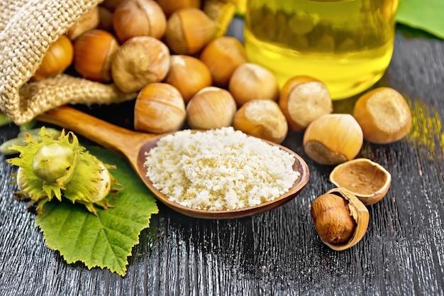 Mąka z orzechów laskowych w łyżce, orzechy w torbie i na stole, olej w szklanym słoiku i gałązka leszczyny z zielonymi liśćmi na tle ciemnej drewnianej deski
