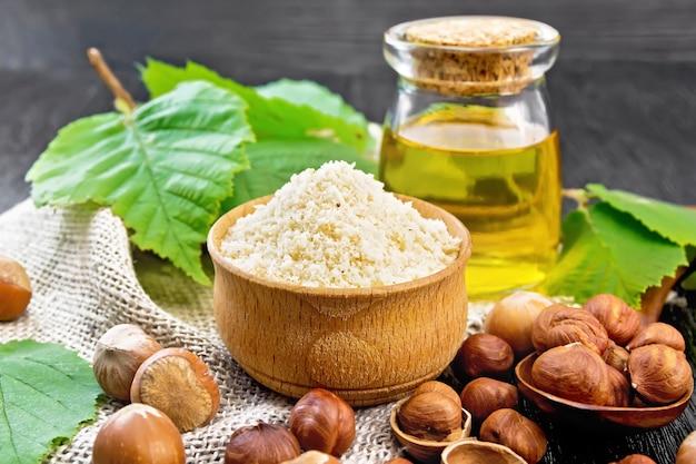 Mąka z orzechów laskowych w misce, orzechy w łyżce, olej w szklanym słoju i gałązka leszczyna