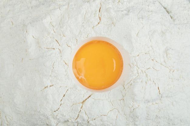 Mąka z surowym żółtkiem na szarym tle.