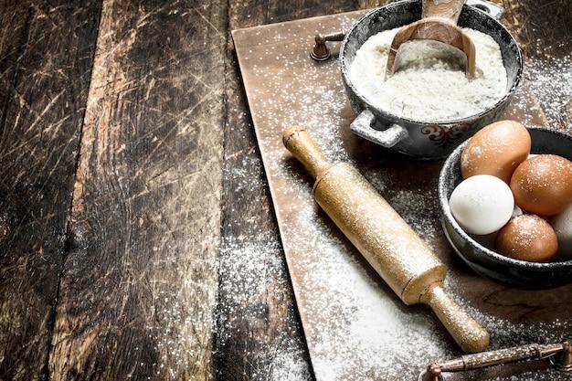 Mąka ze świeżymi jajkami. na drewnianym tle.