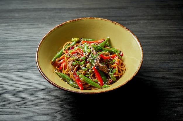 Makaron azjatycki z wołowiną, warzywami, sezamem i sosem teriyaki. street food - wok z makaronem