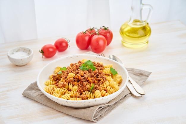 Makaron bolognese. fusilli z sosem pomidorowym, mielona mielona wołowina