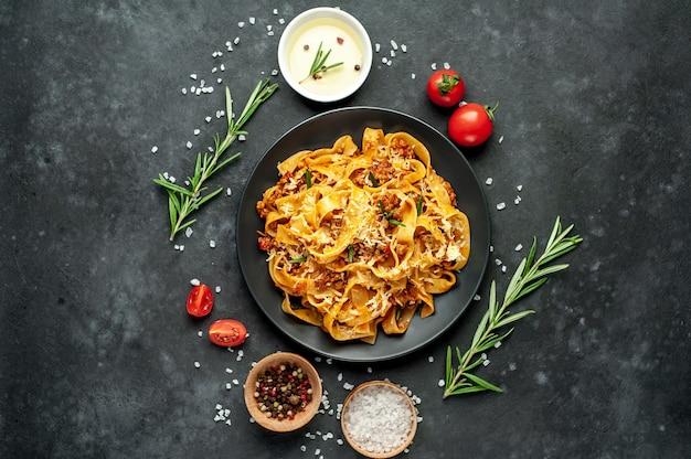 Makaron bolognese z przyprawami, włoskie danie z makaronem z mięsem mielonym i pomidorami w ciemnym talerzu na kamiennym tle