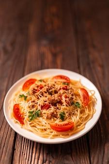 Makaron bolognese z sosem pomidorowym i mielonym mięsem, tartym parmezanem i świeżą pietruszką - domowy zdrowy włoski makaron