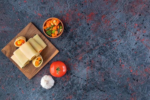 Makaron calamarata nadziewany posiekanymi warzywami na drewnianej desce.
