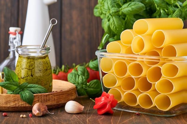 Makaron cannelloni w brązowym papierze na starym tle z oliwą z oliwek, sosem pesto, bazylią i czosnkiem