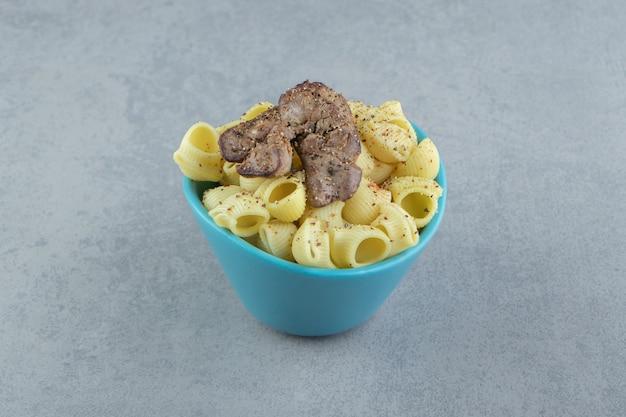 Makaron conchiglie i grillowane mięso w niebieskiej misce