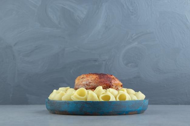 Makaron conchiglie i grillowany kurczak na niebieskim talerzu.