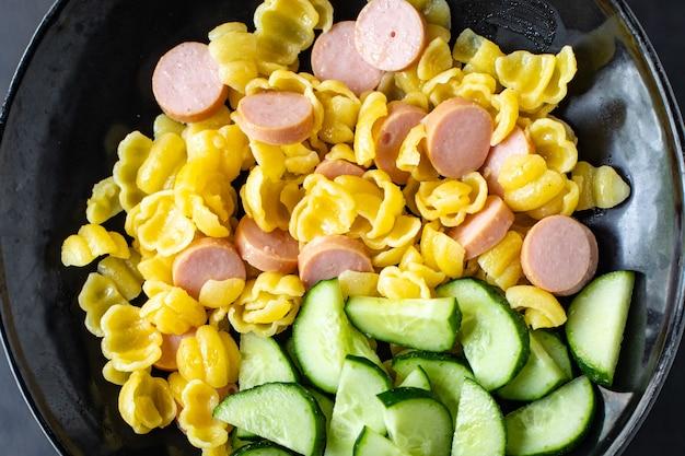 Makaron conchiglie kiełbasy sałatka ogórkowa warzywa