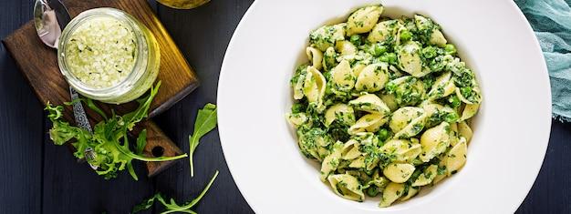 Makaron conchiglie ze szpinakiem i pesto z zielonego groszku. kuchnia włoska. wegańskie jedzenie. transparent. widok z góry