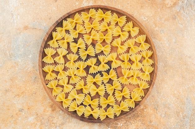Makaron farfalle na drewnianym talerzu na niebieskiej powierzchni