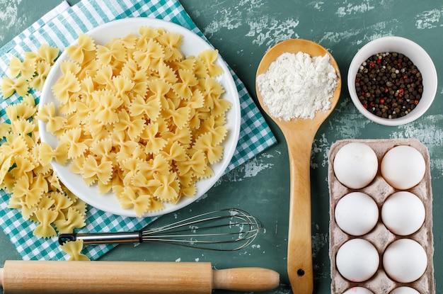 Makaron farfalle z jajkami, wałkiem do ciasta, trzepaczką, pieprzem i skrobią
