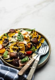 Makaron farfalle z pieczarkami, bazylią, pomidorami i sosem śmietanowym. włoska tradycyjna kuchnia. jedzenie środziemnomorskie