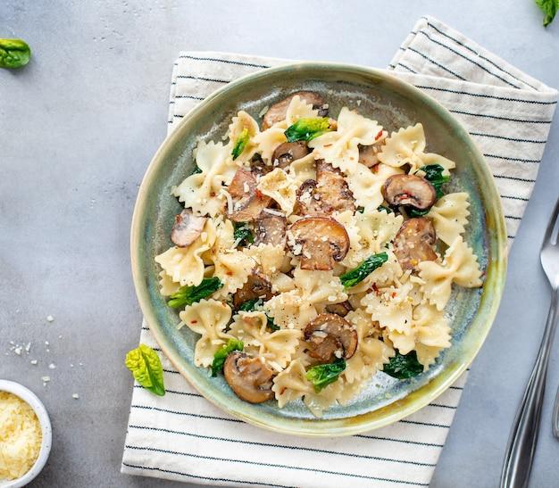 Makaron farfalle z pieczarkami i szpinakiem, podawany na talerzu ceramicznym. szara powierzchnia. kuchnia śródziemnomorska. widok z góry.