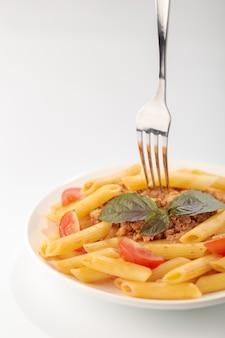 Makaron fettuccine bolognese z sosem pomidorowym i bazylią w białym naczyniu na białym tle
