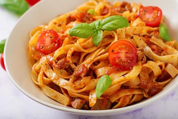Makaron fettuccine bolognese z sosem pomidorowym w białej misce.