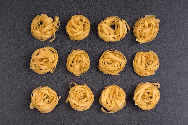Makaron fettuccine tagliatelle na szarym tle. gniazda spaghetti. surowy składnik tradycyjnej kuchni włoskiej