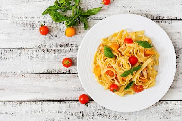 Makaron fettuccine w sosie pomidorowym z kurczakiem, pomidorami ozdobionymi bazylią na drewnianym stole