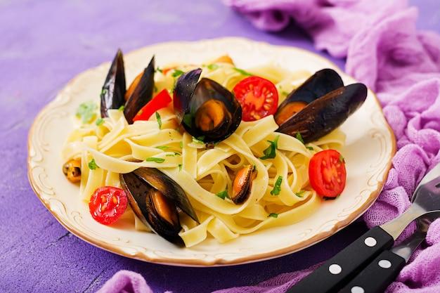 Makaron fettuccine z owocami morza z małżami. przysmaki kuchni śródziemnomorskiej.