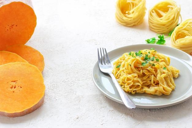 Makaron fettucine z dyni i alfredo w ceramicznym talerzu ze świeżymi, surowymi plasterkami dyni piżmowej. jesienny posiłek na lunch. przepis na squash butternut.
