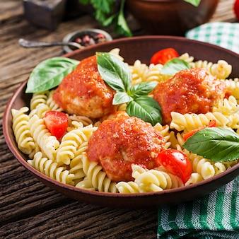 Makaron fusilli z klopsikami w sosie pomidorowym i bazylią w misce, kuchnia włoska.