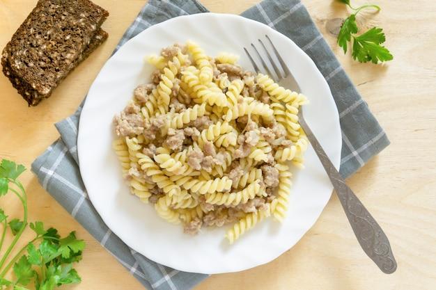 Makaron fusilli z mięsem mielonym na białym talerzu, widok z góry.