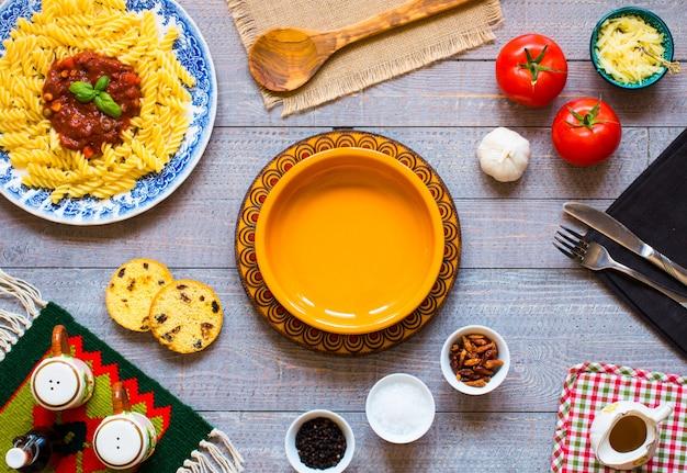 Makaron fusilli z sosem pomidorowym, pomidorami, cebulą, czosnkiem, suszoną papryką, oliwkami, pieprzem i oliwą z oliwek, na drewnianym stole