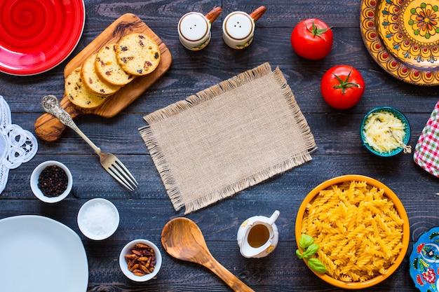 Makaron fusilli z sosem pomidorowym, pomidorami, cebulą, czosnkiem, suszoną papryką, oliwkami, pieprzem i oliwą z oliwek na drewnianym stole